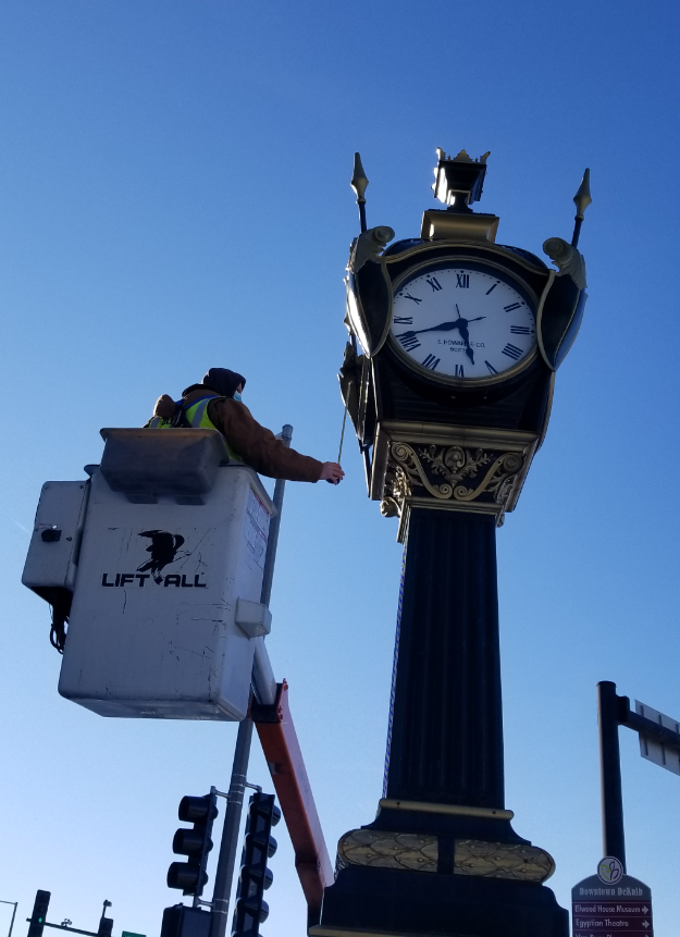 Image of a person in a bucket lift inspecting the DeKalb Soldiers and Sailors Memorial Clock